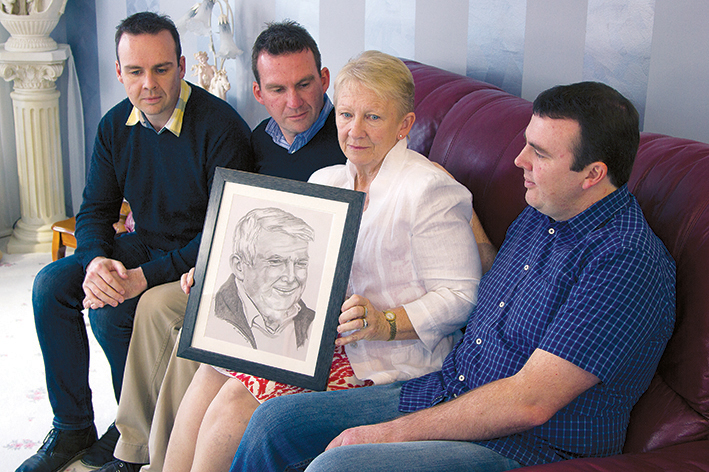 A shattered family: Dale, Christian, Bridget and Trent O'Toole with a drawing of Dermot that hangs in the family loungeroom. Picture: Cameron McCullough
