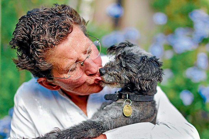 Loving cuddle: Owner Maggie Brown gives Sammy a hug after his ordeal. Picture: Yanni
