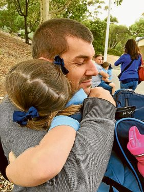 Loving father and husband: Mr Matthews hugs his daughter Annabel on her first day of school this year.