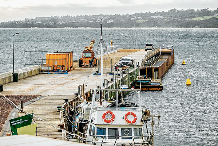 Not long now: Parks Victoria contractors put the finishing touches to the outer, 75-metre section of Mornington pier on Friday. Ports minister Luke Donnellan is this week expected to announce the opening date, weather permitting. Picture: Yanni
