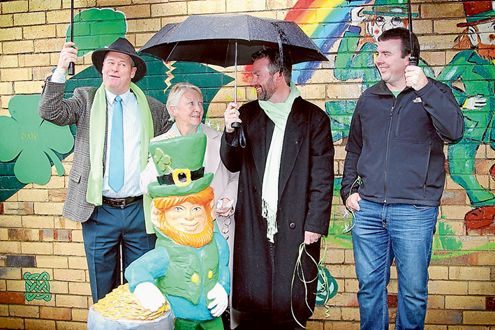 Lots of rain, but memories shine: Councillor David Garnock (left), Bridget O'Toole with two of her sons, Christian and Trent. They stand behind a leprechaun carving by Angie Polglaze. Picture: Cameron McCullough