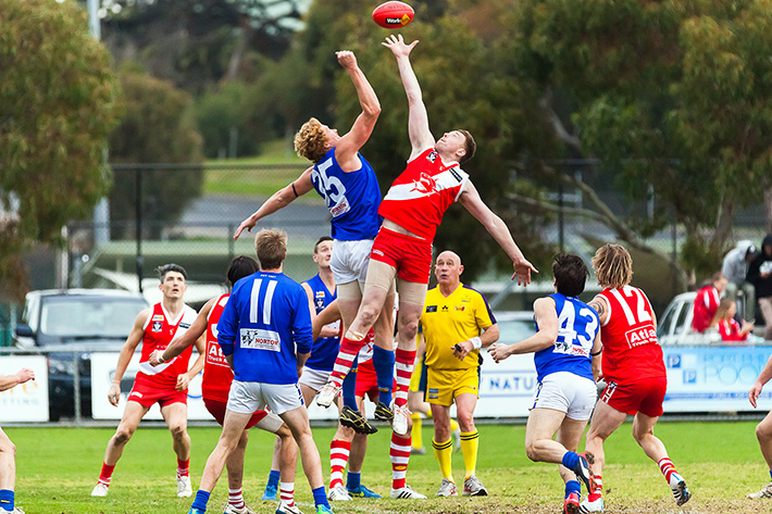 Eyes on the pill: Sorrento got up over Hastings in Saturday's Nepean League clash, left, with a final quarter eight-goal burst enough to see the Sharks over the line against the Blues. Picture: Andrew Hurst