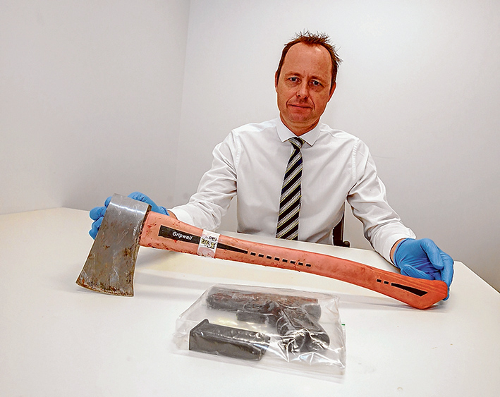 Weapons query: Detective Al Hanson, of Frankston Embona Armed Robbery Task Force, displays the axe and a handgun allegedly used in the 7-Eleven robberies.
