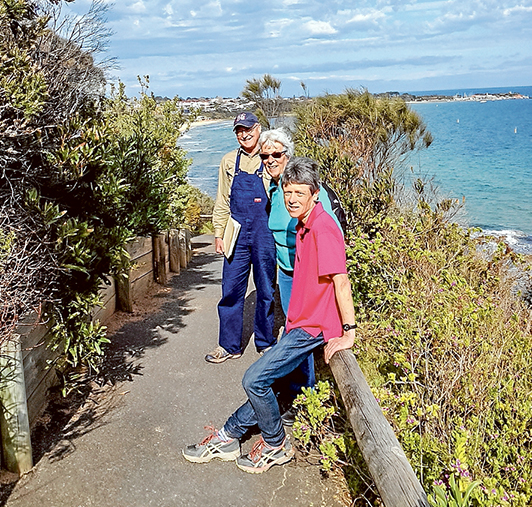 """Track fans: Peter Nicholson, left, Barbara Johnston and Kate Philip of the Caraar Creek Coastal Cliff Pathway steering committee on the """"goat track"""" overlooking Mills Beach (left) and Mornington harbour. They want the shire and state government to repair the iconic, 100-year-old track. Picture supplied"""