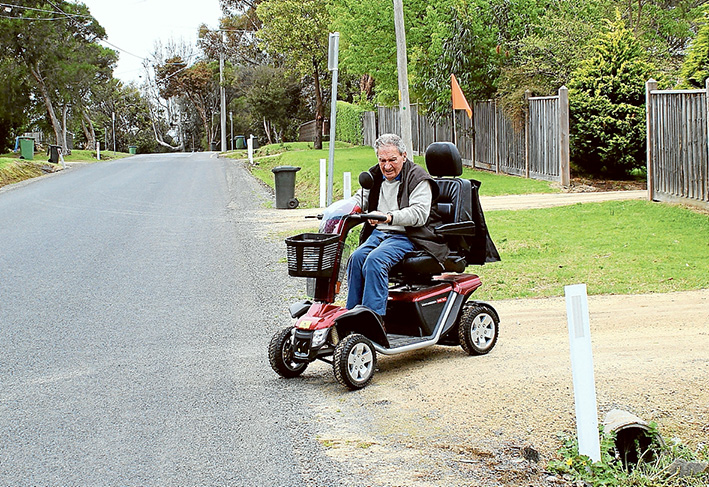 Footpath needed: Somers resident Doug Coates says a made footpath in the village cannot come soon enough. A Somers resident for 33 years, Mr Coates has to use the road to get from his house to anywhere in Somers on his mobility scooter. He says he cannot drive over the nature strips, despite buying a larger scooter with wider wheels, and is forced onto the road, competing with cars and buses.
