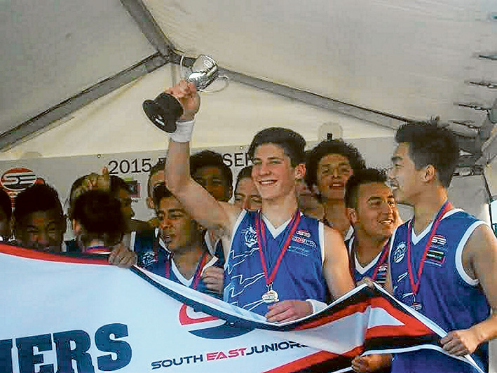 It's ours: Perry Lewis-Smith celebrates his football premiership win with team mates.