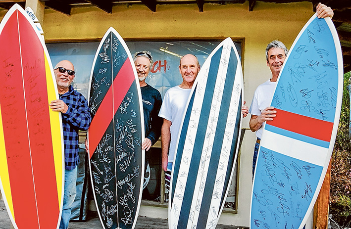 """Signed up: Four of the """"footy boards"""" to be auctioned to raise money for the Disabled Surfers Association Mornington Peninsula branch with, from left, branch president Joe Hart, Rod Jones (Triple R's Dr Surf), boardmaker Phil Trigger and committee member John Bowers."""