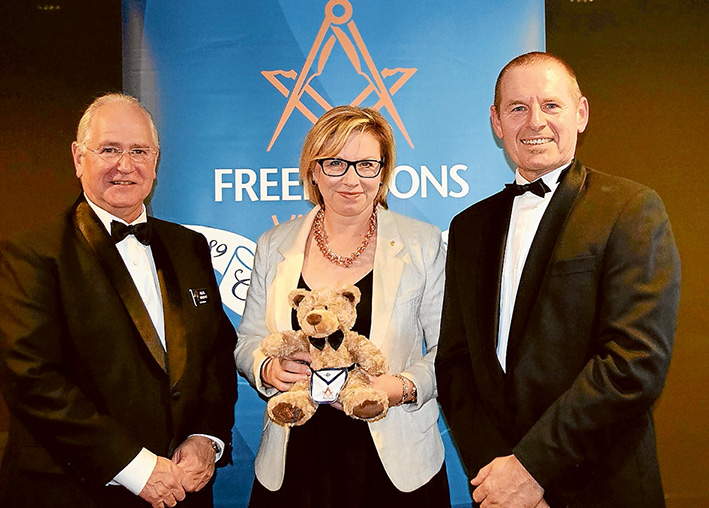 """Like minds: Grand Master Freemasons Victoria Hellel Benedykt, Australian of the Year Rosie Batty, and Master of Mornington Lodge Edy Wilfling with Lewis the Bear. He has been sold to raise money for the """"Never Alone"""" Luke Batty Foundation. Picture: Marg Harrison"""