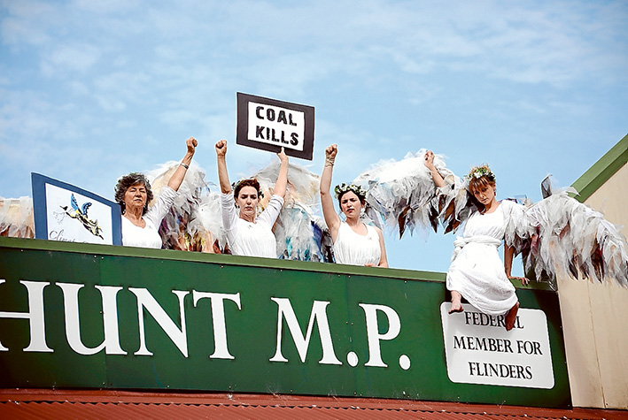 Angels on high: Climate Guardians clambered to the roof over MP Greg Hunt's Hastings office on Friday afternoon as part of the ongoing activism against the federal government's positive policies towards coal mining. Picture: Jarryd Bravo
