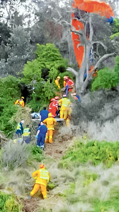 Complex task: Emergency services teams rescue a hang-glider who became tangled in a dead tree on the cliff at Flinders Golf Course on Sunday last week. Picture: Sorrento SES