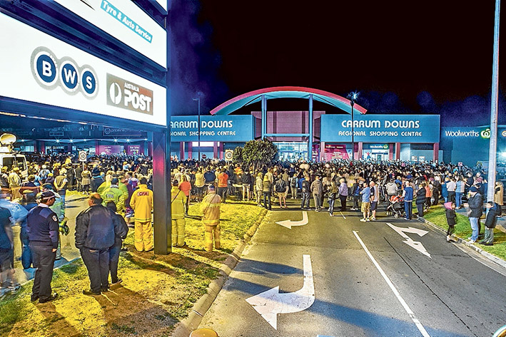 Tributes after tragedy: The community rallied round to show support for the Lehane family in the wake of Andrea Lehane's death by laying flowers, below right, and attending a vigil, above, at Carrum Downs Regional Shopping Centre. Pictures: Gary Sissons