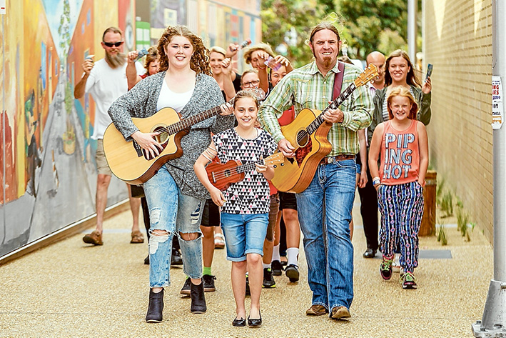 Fan following: musicians Lily Short, Madison Bailey and Andy Phillips busk their way along the streets of Rosebud with some of their fans. Picture: Yanni