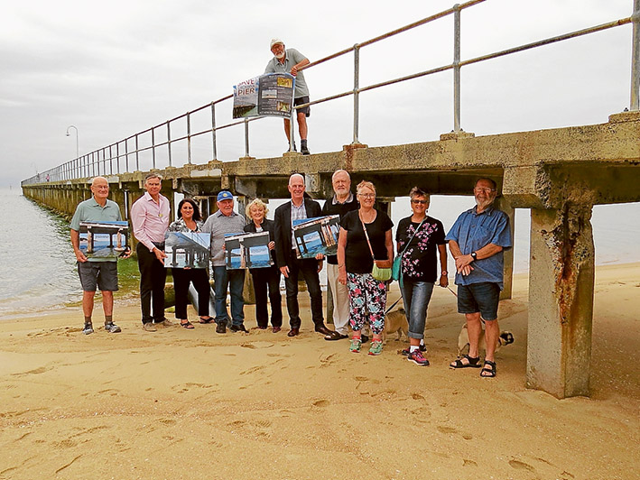 Group pressure: Save Dromana Pier supporters show their reasons for campaign for a new pier while standing next to a crumbling pylon.