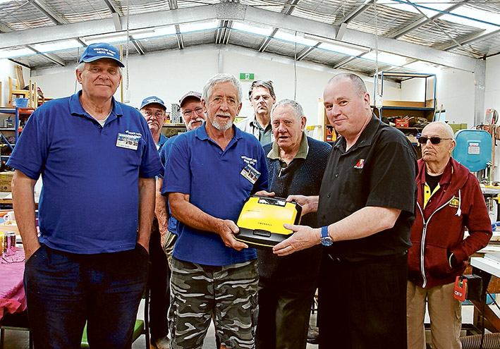 Life saver: Western Port (Hastings) Men's Shed secretary Colin Proud (centre, in blue) and training officer Andrew Clinkaberry show off the new defibrillator.