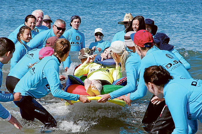 Team effort: Many hands are involved during surfing for the disabled events at Point Leo, but non wave more than the delighted board riders. Picture: Keith Platt