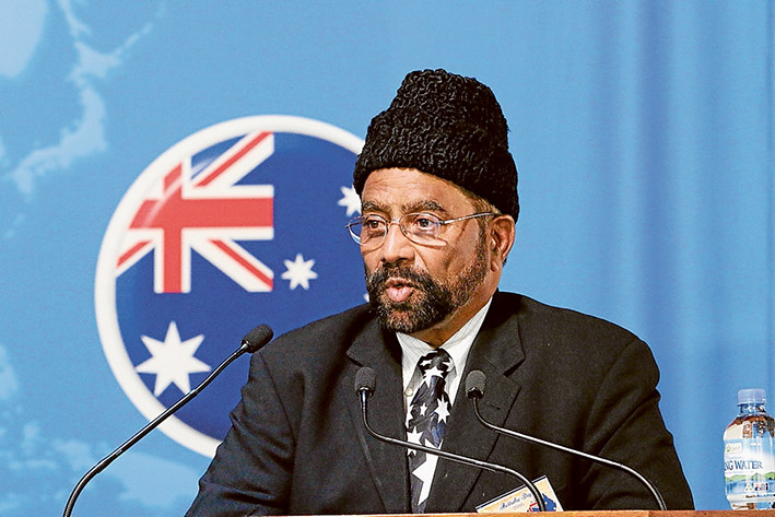 """Loyal children: Imam Inamul Haq Kauser, above, says children of Ahmadi Muslims will be Australia's """"best citizens""""; children at the Baitu-us-Salam (House of Peace) Mosque, Langwarrin, sing the national anthem during an Australia Day dinner, below. Pictures: Supplied"""