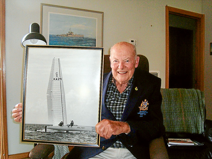 """All abuzz: John Buzaglo of Mornington was awarded the Medal of the Order of Australia on 26 January for services to yachting. He is holding a photo of Miss Nylex, the """"wingsail"""" catamaran that revolutionised international yacht racing including the modern America's Cup. Picture supplied"""