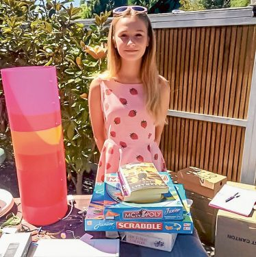 Out they go: Lily Ford mans the stall, with funds raised to help her former teacher's special charity.