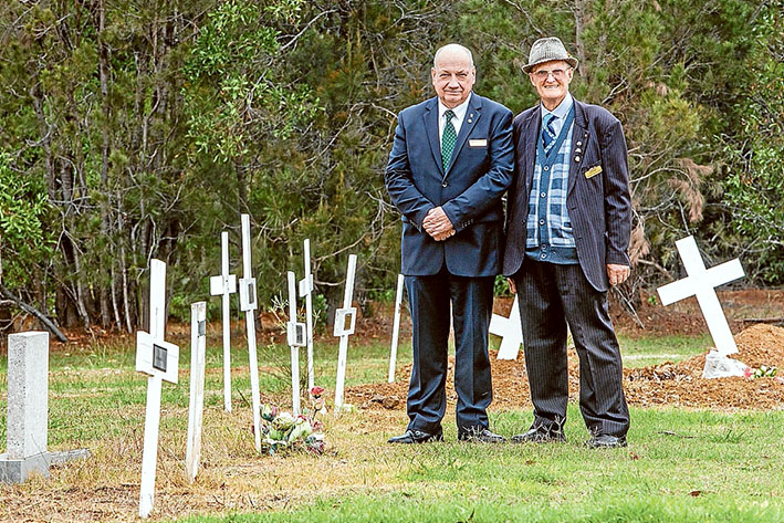 """Fitting send-off: Funeral director Brian McMannis and Crib Point Cemetery treasurer Clem Kleinig beside crosses marking the """"paupers"""" graves. Picture: Gary Sissons"""