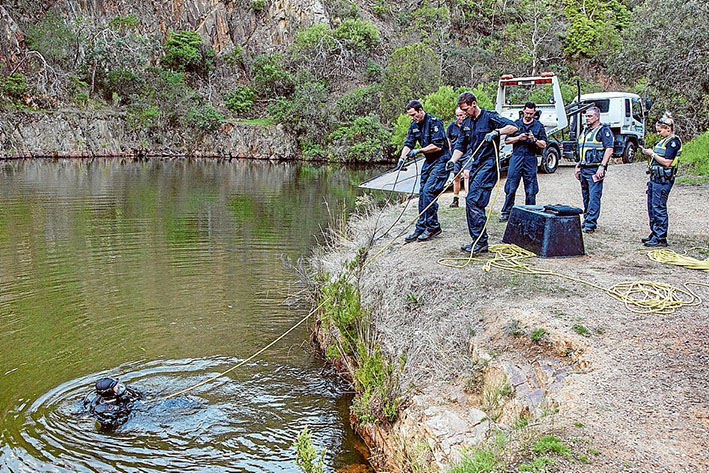 Making a splash: Police search for a car reported by early morning walkers who saw it sink in Moorooduc quarry soon after it was driven through a gate from Station St, Mt Eliza. Picture: Gary Sissons