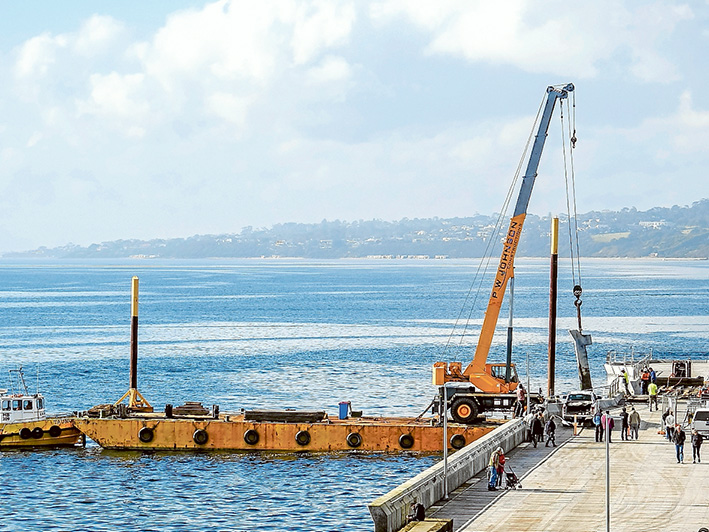 A crane aboard a barge is used to lift 15 tonne concrete panels which broke off Mornington pier during a stome two weeks ago. Picture: Yanni