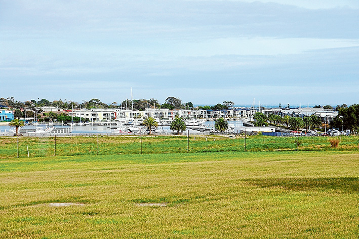 """Close community: The green fields leading to the water's edge at Martha Cove are earmarked for three-storey """"townhomes"""" and shops, above; while, below, houses and apartments are already nearing completion overlooking the next staged development."""