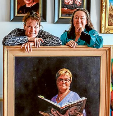"""Doubling up: Fiona Bilbrough and Vicki Sullivan have combined their works for a portraits exhibition at Mornington Peninsula Regional Gallery. Theyt are pictured with Bilbrough's """"Attention Please"""" portrait of  former primary school principal, Carol Norman. Picture: Supplied"""