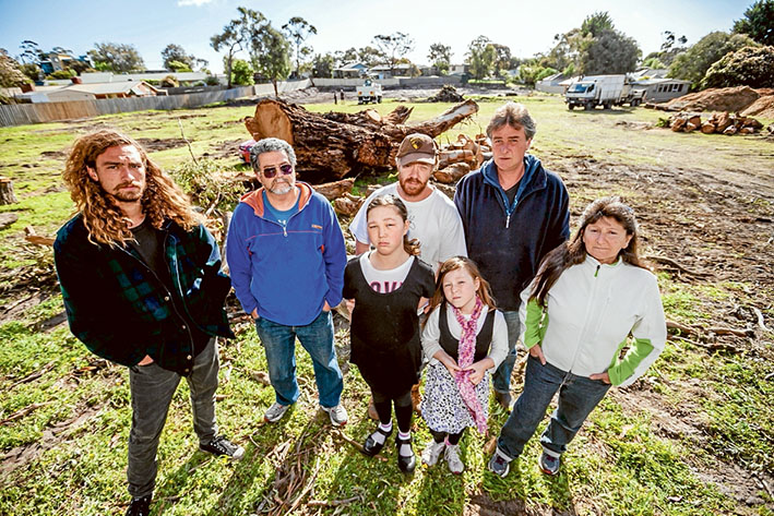 Jason Legg, Mal Campbell, Craig Thomson, Mal Legg, Dorris Campbell and Rose and kids Eve Thomson, left, with the remains of the aged eucalypt. Main picture: Yanni
