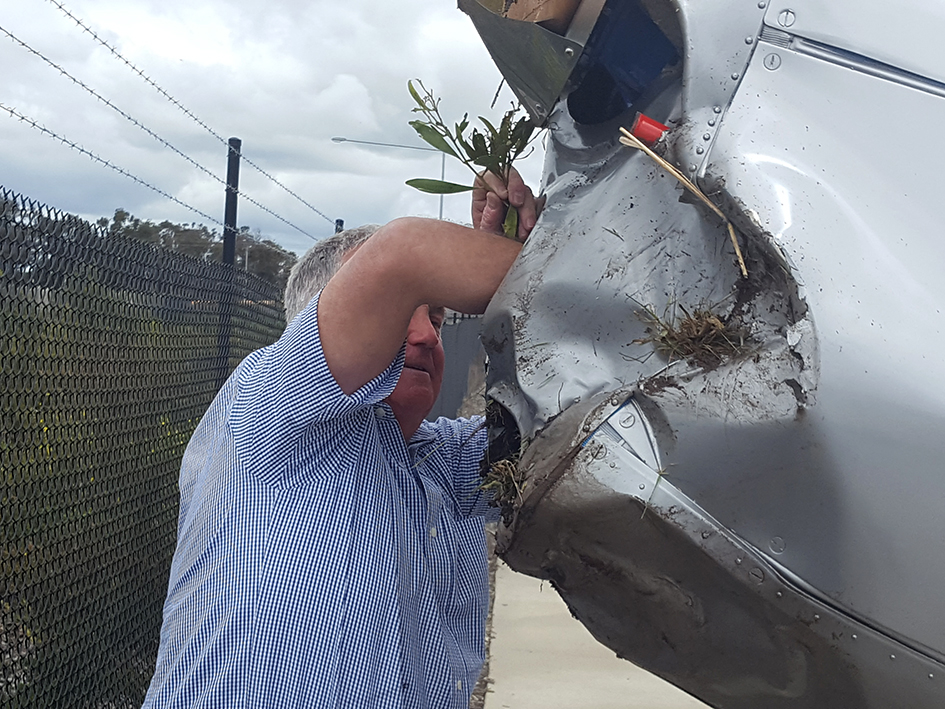 Graham Hosking removes debris from the intake at the front of his crashed plane. Picture: Cameron McCullough