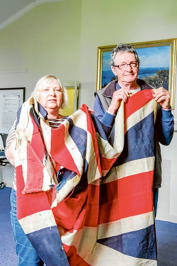 Flag bearers: Dromana and District Historical Society president Jean Rotherham and historian Fred Wild with the Union Jack that renowned artist Ewart Melbourne Brindle took to the United States in 1918, above, and drawing books from his days at Dromana State School. Pictures: Keith Platt